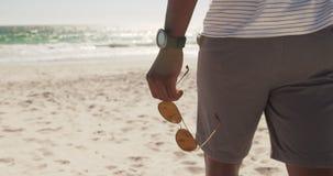 Mann, der auf den Strand 4k geht stock footage