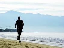 Mann, der auf den Strand läuft stockbild