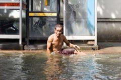 Mann, der auf der Straße während der Flut sitzt lizenzfreie stockbilder
