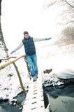 Mann, der auf die dünne Fußbrücke geht stockfoto