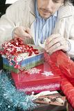 Mann, der auf die Geschenk-Verpackung sich konzentriert Lizenzfreie Stockfotografie