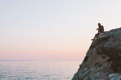 Mann, der auf die Klippenoberseite sitzt Lizenzfreie Stockbilder