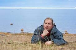 Mann, der auf die Seeküste legt Stockfotos