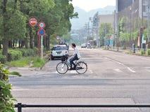 Mann, der auf die Straße radfährt Stockbild