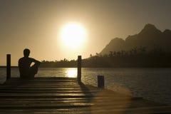 Mann, der auf Dock durch See sitzt Stockfotografie