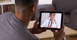 Mann, der auf Doktor auf Tablette hört Lizenzfreies Stockfoto