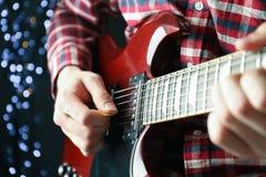 Mann, der auf E-Gitarre gegen dunklen Hintergrund spielt lizenzfreies stockfoto