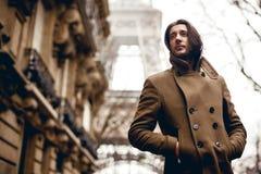 Mann, der auf Eiffelturmhintergrund aufwirft stockfotografie