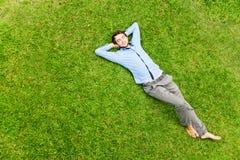 Mann, der auf ein Gras legt Stockbild