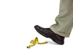 Mann, der auf eine Bananenschale geht Stockfotografie