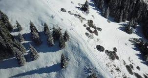 Mann, der auf eine schneebedeckte Steigung geht Ansicht vom Brummen, Schießen Draufsicht eines Mannes in den Bergen stock footage