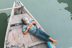 Mann, der auf einem alten hölzernen Boot schläft Stockfotos