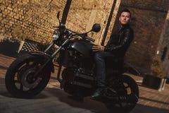 Mann, der auf einem CaféRennläufermotorrad sitzt Stockfotografie