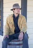 Mann, der auf einem Faß sitzt Lizenzfreie Stockbilder