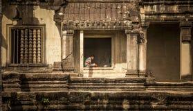 Mann, der auf einem Fenster von Angkor Wat sitzt stockfoto