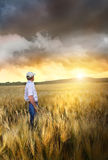 Mann, der auf einem Gebiet des Weizens steht Lizenzfreies Stockfoto