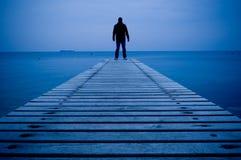 Mann, der auf einem hölzernen Pier steht stockfotografie