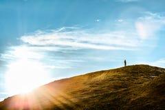 Mann, der auf einem Hügel im Sonnenlicht denkt steht Lizenzfreies Stockfoto