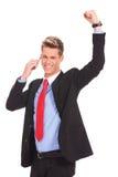 Mann, der auf einem Handy und einem Gewinnen behandelt Lizenzfreie Stockfotografie