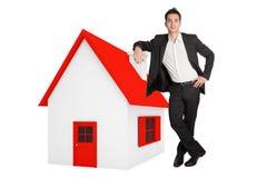 Mann, der auf einem minitaure Haus sich lehnt lizenzfreies stockfoto