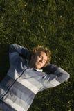 Mann, der auf einem Rasen liegt stockbild