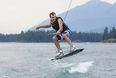 Mann, der auf einem schönen Gebirgssee wakeboarding ist lizenzfreie stockfotografie