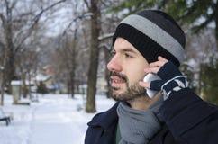 Mann, der auf einem Smartphone im Winter spricht stockbild