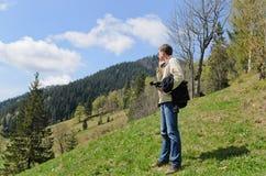 Mann, der auf einem steilen grasartigen steht Stockbild