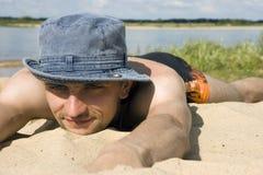 Mann, der auf einem Strand liegt Stockfotografie