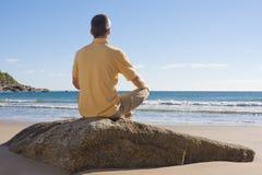 Mann, der auf einem Strand meditiert lizenzfreie stockbilder