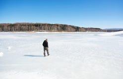 Mann, der auf einen gefrorenen See geht stockfotos