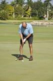 Mann, der auf einen Golfplatz sich setzt Lizenzfreies Stockfoto