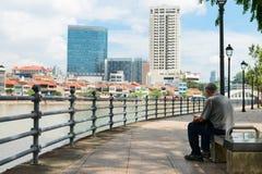 Mann, der auf einer allgemeinen Bank mit Blick auf städtisches Singapur sitzt Lizenzfreies Stockfoto