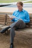Mann, der auf einer Bank mit Gerichtsakten in seiner Hand sitzt Lizenzfreie Stockbilder