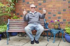 Mann, der auf einer Bank sitzt Stockbild
