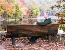 Mann, der auf einer Bank sitzt Stockfotografie