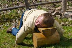 Mann, der auf einer Holzbank schläft Lizenzfreies Stockfoto