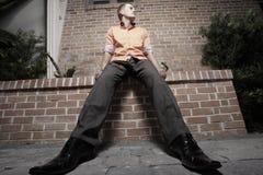 Mann, der auf einer Leiste sitzt Stockbilder