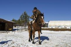 Mann, der auf einer Pferderückseite klettert Stockfotografie