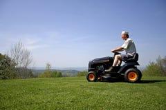 Mann, der auf einer Rasenmähmaschine sitzt Lizenzfreies Stockfoto