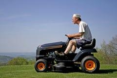 Mann, der auf einer Rasenmähmaschine sitzt Lizenzfreies Stockbild