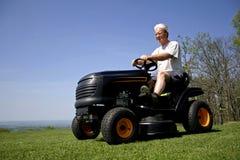Mann, der auf einer Rasenmähmaschine sitzt Stockbilder