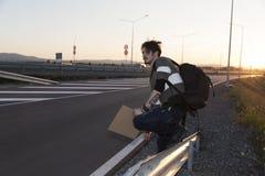 Mann, der auf einer Straße per Anhalter fährt Stockbilder