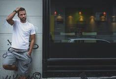 Mann, der auf einer Wand aufwirft Stockfotos