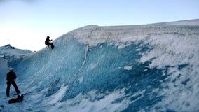 Mann, der auf Eisberg klettert stockfotos
