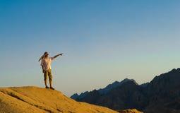 Mann, der auf Felsen-Gipfel in der Wüste steht Stockbild