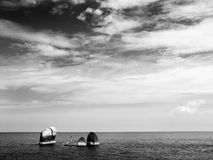 Mann, der auf Felsen im Ozean feiert Lizenzfreies Stockfoto