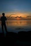 Mann, der auf Fischen bei Sonnenuntergang sitzt Lizenzfreie Stockfotografie