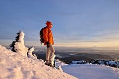Mann, der auf Gebirgsaufpassendem Spitzensonnenuntergang snowshoeing ist Lizenzfreie Stockfotografie