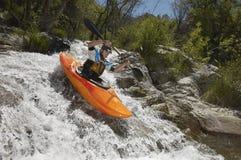 Mann, der auf Gebirgsfluss Kayak fährt Lizenzfreie Stockfotos